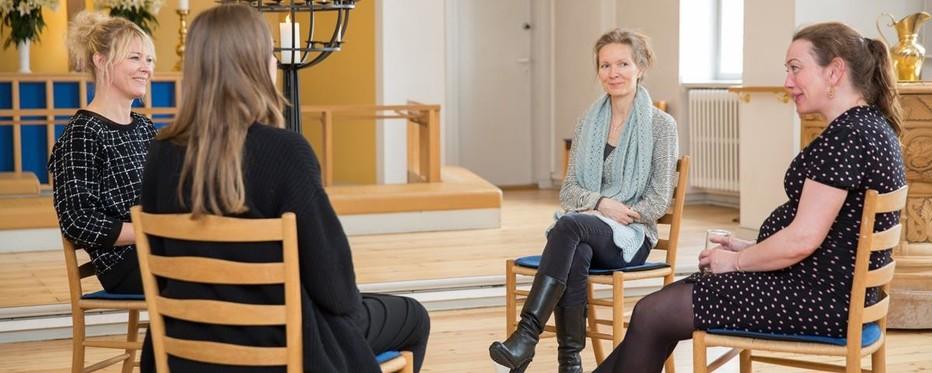 To kvinder og en præst og en jordemoder samlet i en rundkreds til samtale