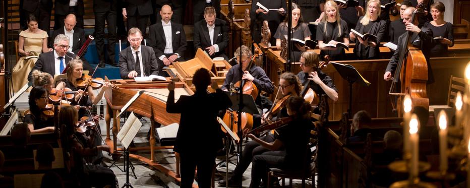 Orkester og kort optræder i et kirkerum