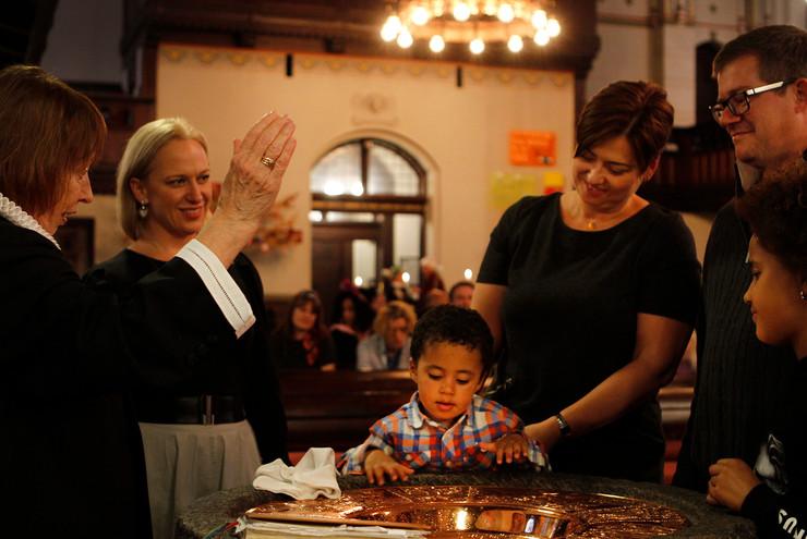 Præst ved døbefonten sammen med dåbsbarn og familie