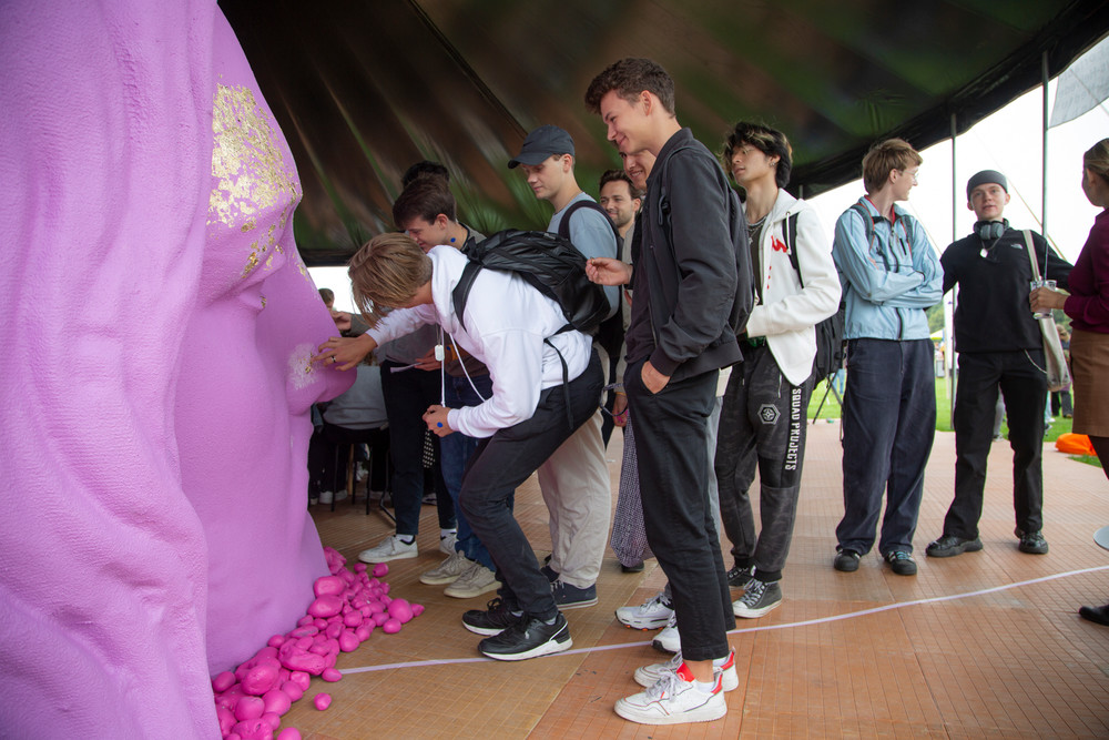 en gruppe unge foran et pink Jesushoved