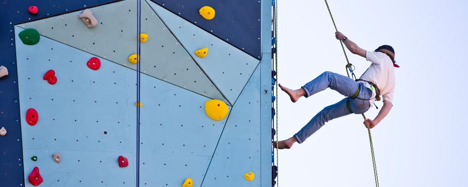 Stemningsbillede af en mand i klareudstyr på vej op ad klatrevæg