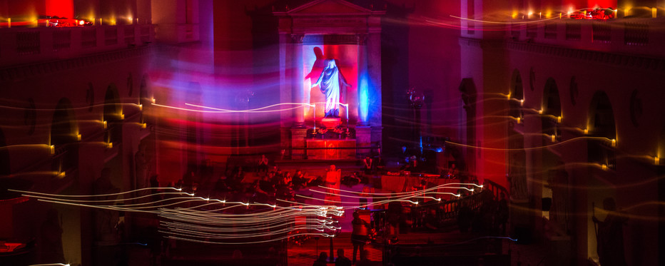 Stort kirkerum  oplyst i mange forskellige farver. Rundt på gulvet af kirken sidder mennesker i grupper