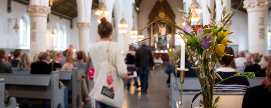 Mennesker på vej op ad kirkegulv i en fyldt kirke. En buket blomster i forgrunden