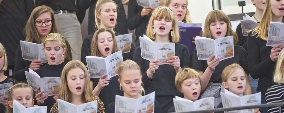 Piger der synger kor med noder i hænderne