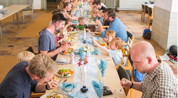 Mange forældre og børn samlet omkring et langt bord i en kirke