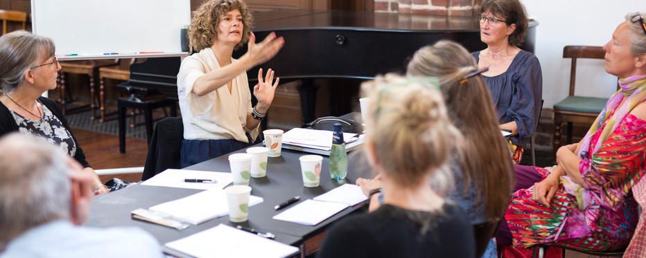 Gruppe af mennesker taler sammen omkring et bord
