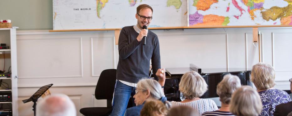 Mand med med en mikrofon i hånden holder foredrag for en gruppe mennesker