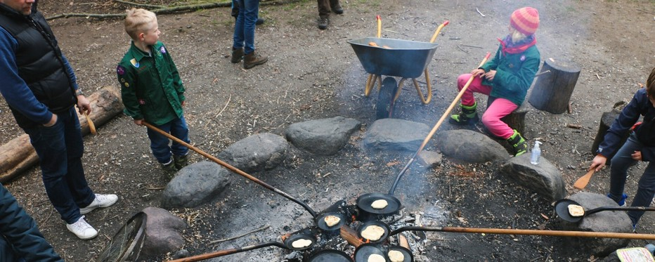 KFUM-Spejdere omkring et lejrbål med bålpander