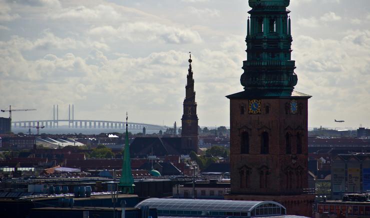 Udsigt over Københavns tage og kirkespir med Øresundsbroen i baggrunden.