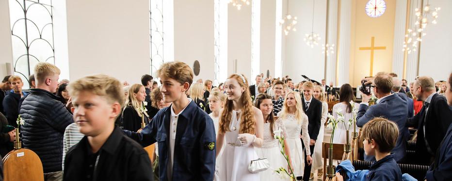 Em flok unge konfirmander på vej ned ad kirkegulvet efter deres konfirmation