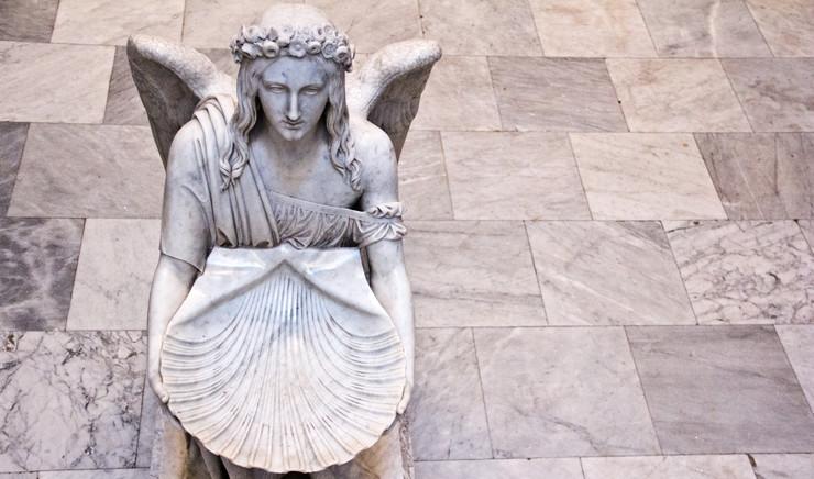Døbefont formet som en knælende engel i marmor