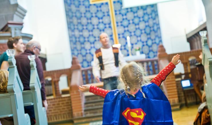 Lille pige i supermandskostume i en kirke