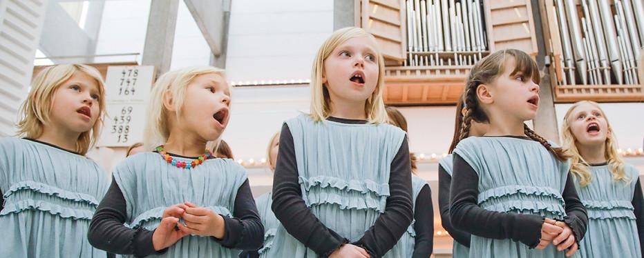 Børn der synger kor foran et orgel