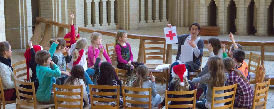 Børn sidder i en rundskreds i en kirke og lytter på en voksen