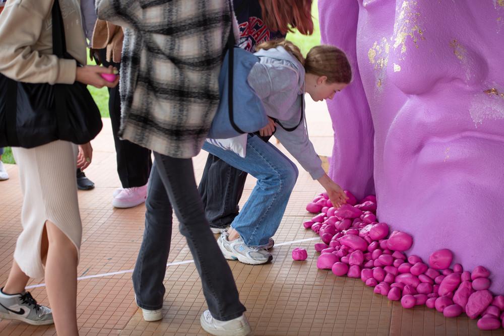 en gruppe unge lægger pink sten foran et pink Jesushoved