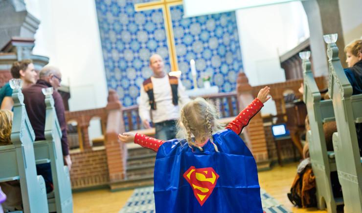 Lille pige i supermandskostume på vej op ad kirkegulv