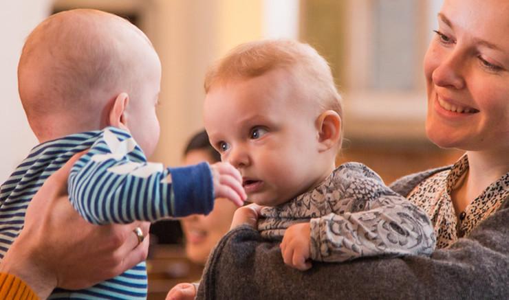 En kvinder holder sin baby hen mod en anden baby