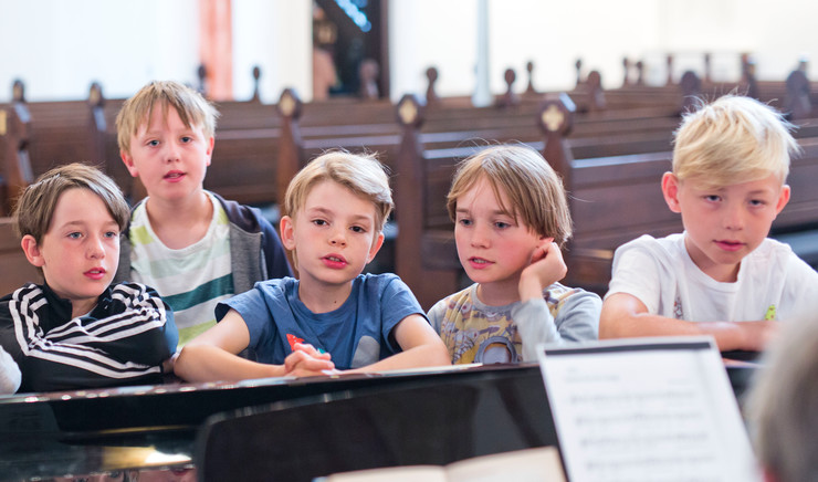 Børn samlet omkring et flygel i en kirke